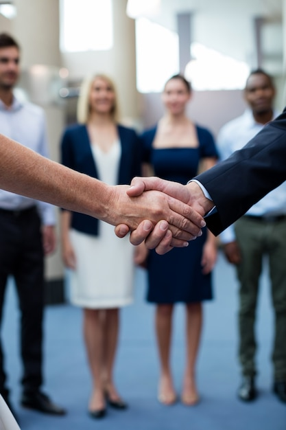 Business executives shaking hands with each other Premium Photo