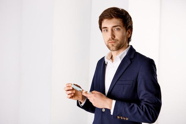 Бизнес, финансы и концепция дохода. красивый богатый мужчина предприниматель стоит в офисе, носит костюм, считает деньги, держит наличные и выглядит серьезно Бесплатные Фотографии