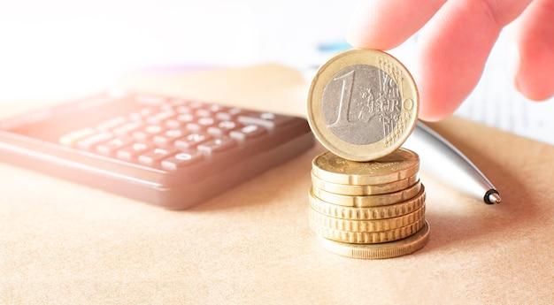 Бизнес, финансы или инвестиционная концепция. монеты, чековая книжка или записная книжка и перьевая ручка, калькулятор. Premium Фотографии