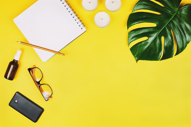 Business flatlay with mobile phone, glasses, philodendron leaf and other accessories. yellow background. Premium Photo