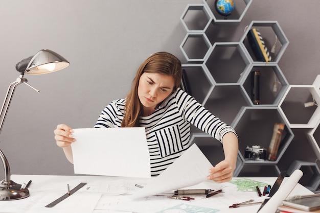 Бизнес, внештатный, концепция совместной работы. молодой симпатичный смущенный женский архитектор сидит в коворкинг месте, разговаривает по телефону с клиентом, пытаясь найти информацию в документах. Бесплатные Фотографии