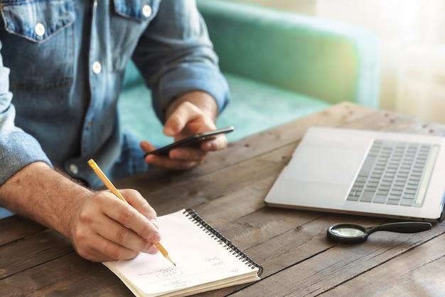 스마트 폰 및 노트북 집에서 일하는 비즈니스 프리랜서 남자. 나무 테이블에 노트북에서 쓰는 사람 손을 닫습니다. 원격 작업 개념 프리미엄 사진