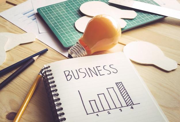 Бизнес-график на ноутбуке с лампочкой на деревянном столе. Premium Фотографии