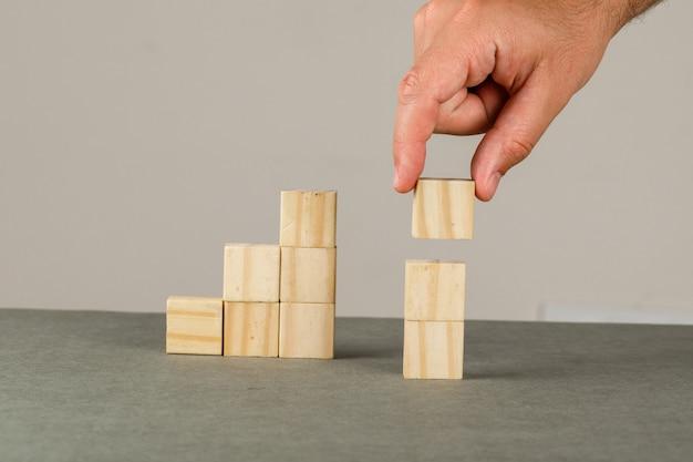 Concetto di crescita di affari sulla vista laterale della parete grigia e bianca. uomo che organizza il blocco di legno che impila la scala. Foto Gratuite