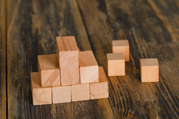 Business growth concept with pyramid of wooden cubes on wooden table high angle view. Free Photo