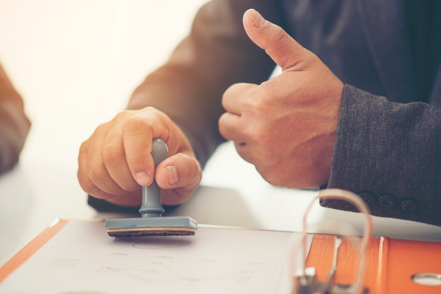 Business hand putting stamp on a document, close up Premium Photo