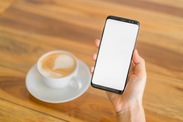 Бизнес-рука с мобильным телефоном и латте-арт-кофе. Бесплатные Фотографии