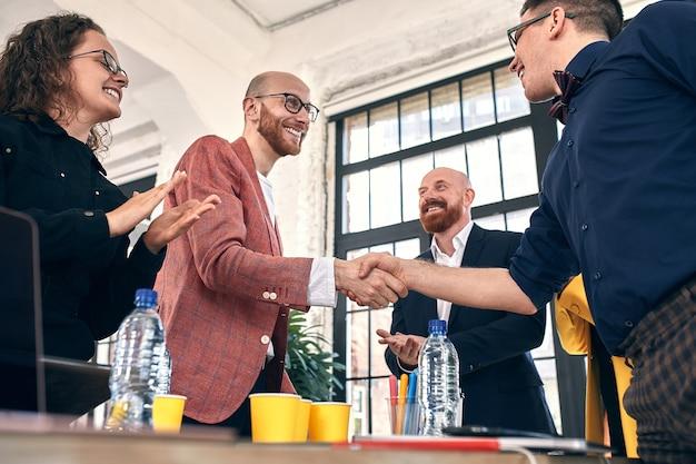 契約書や財務書類に署名することで、オフィスパートナーとの会議や交渉でのビジネスの握手が満たされる Premium写真