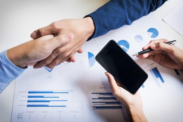 企業、企業、企業間の合意や契約に署名するための合意を示す2人の男性のビジネスハンドシェイク 無料写真