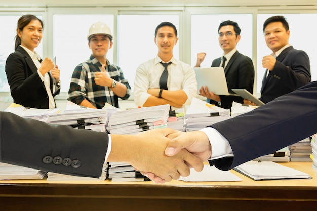 Business handshake successful with pile of paperwork and group of teamwork in background. Premium Photo
