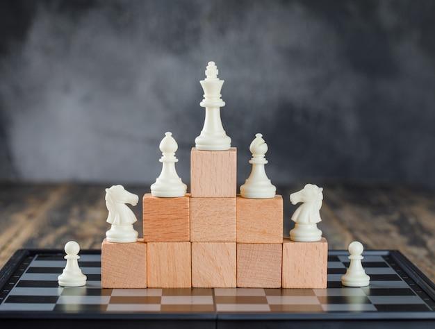 チェス盤、霧と木製のテーブルの側面に木製のブロックのピラミッドの数字とビジネス階層概念。 無料写真