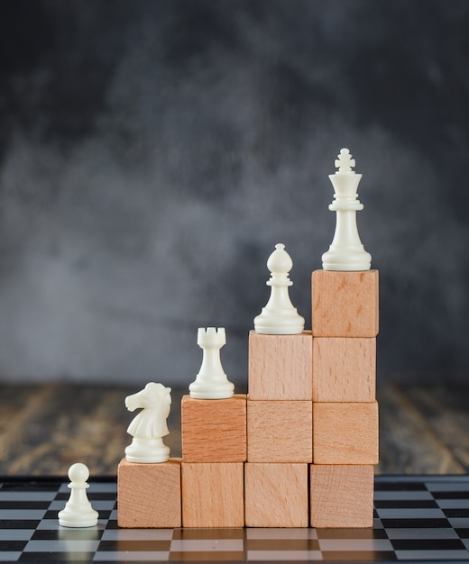 Business hierarchy concept with chessboard, figures, pyramid of wooden blocks on foggy and wooden table side view. Free Photo