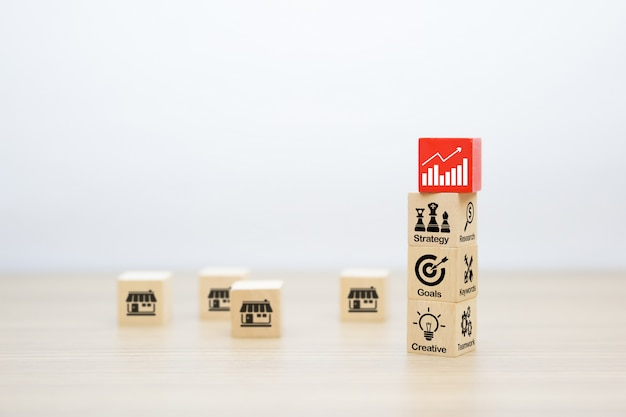 Business icons on wooden cube shape stacked. Premium Photo