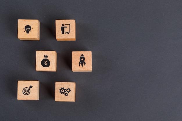 Бизнес-идея концепции с иконками на деревянных кубиков на темно-серый стол плоской планировки. Бесплатные Фотографии