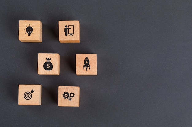 Business idea concept with icons on wooden cubes on dark grey table flat lay. Free Photo
