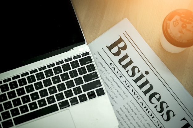 Business ideas concept with newpapaper and laptop with coffee on working desk Premium Photo
