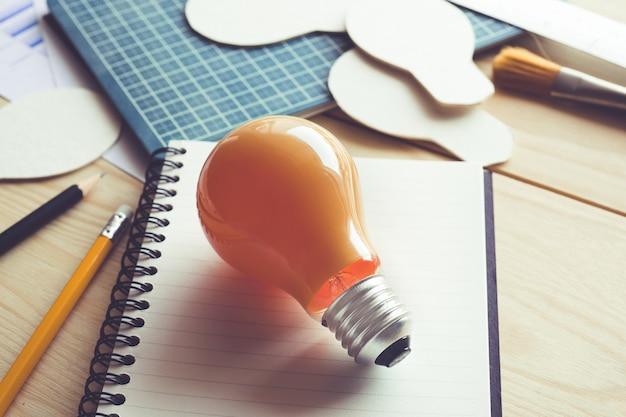 Бизнес-идеи с лампочкой на письменном столе. Premium Фотографии