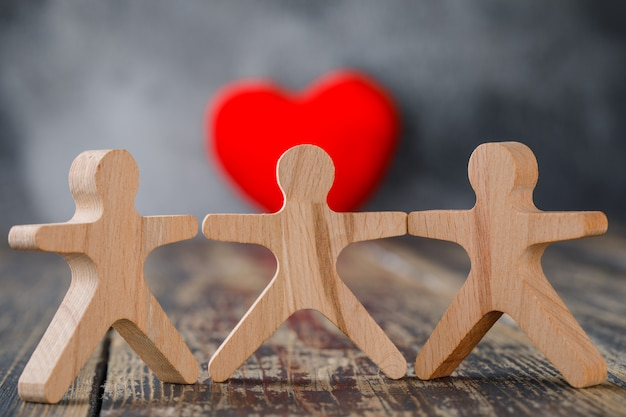 Business and insurance concept with wooden figures of people, red heart close-up. Free Photo