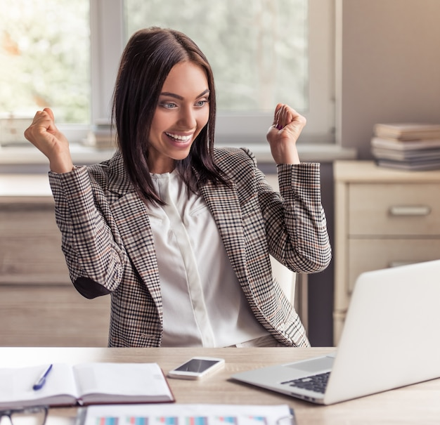 Business lady in formal clothes is looking at laptop. Premium Photo