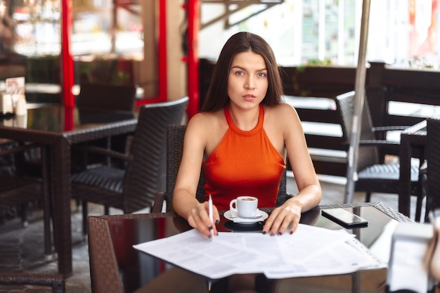 Business lady girl sits at a table in a cafe, considers paper, thinks. resume, signing an important business deal. work away from home. Premium Photo