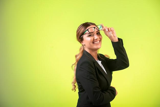 검은 색 재킷과 안경을 쓴 비즈니스 여성은 긍정적으로 보입니다. 무료 사진
