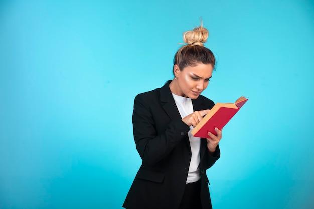赤い本とそれを読んで黒いブレザーのビジネスレディ。 無料写真