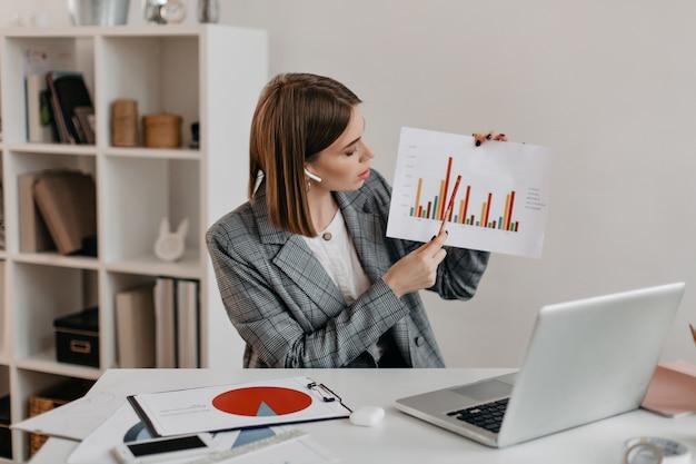 ビジネスレディは、明るい職場に座って、チャートを手に持って、ビデオコミュニケーションを通じてクライアントにそれを伝えています。 無料写真