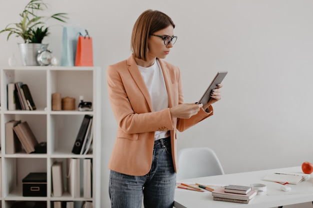 Business lady looks puzzled at tablet. young woman in light clothing posing over office. Free Photo