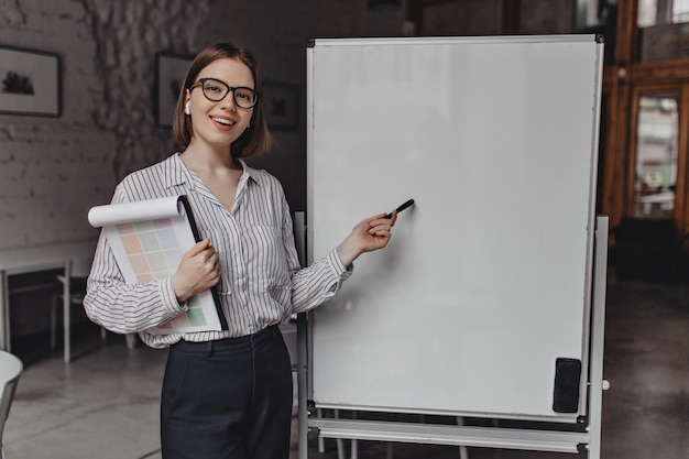 Business lady in strict suit and glasses smiles, holds documents and points to white office board. Free Photo