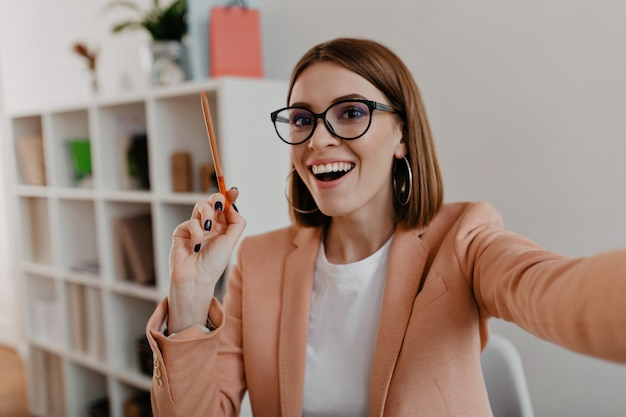 Donna d'affari con gli occhiali e in abito leggero elegante fa selfie, tenendo la matita arancione tra le mani. Foto Gratuite