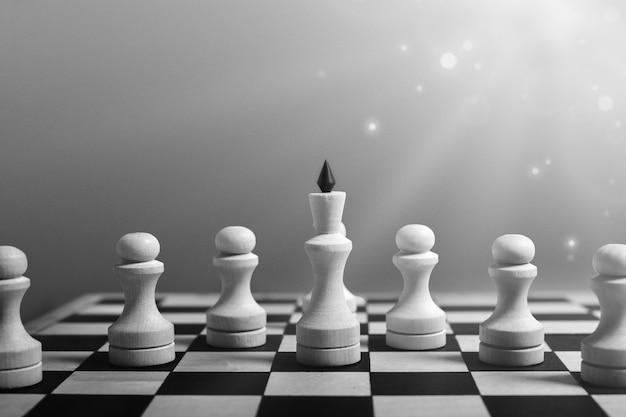 Концепция бизнес-лидерства. белая шахматная королева стоит с пешками, ведущими их к победе. черно-белое, копирование пространства, блики Premium Фотографии