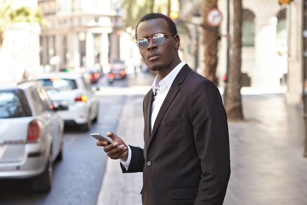 ビジネス、ライフスタイル、現代のテクノロジー。スタイリッシュなフォーマルな服装と色合いで、スマートフォンのオンラインアプリを使用してタクシーサービスをリクエストし、路上に立っている自信のある魅力的な黒肌のceo 無料写真