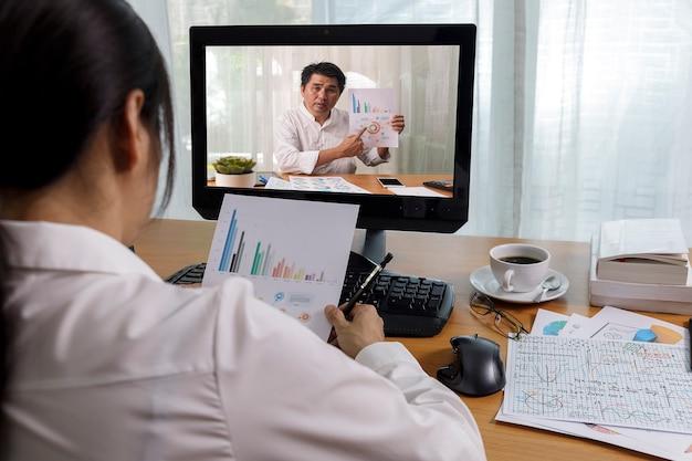Деловой междугородний видеозвонок, анализ финансового отчета бизнесмена и бизнес-леди с использованием приложения видеоконференции для виртуального общения Premium Фотографии