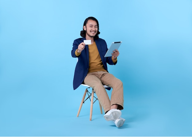 Business man asian happy smiling showing credit card and using a digital tablet while sitting on chair on bright blue. Free Photo