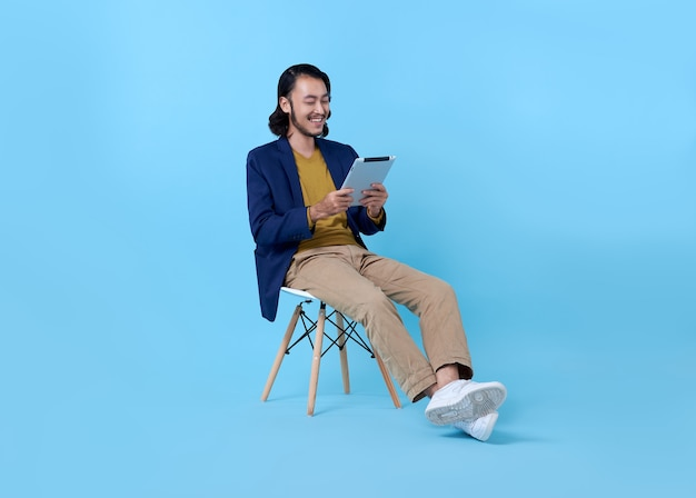 Business man asian happy smiling using a digital tablet while sitting on chair on bright blue. Free Photo