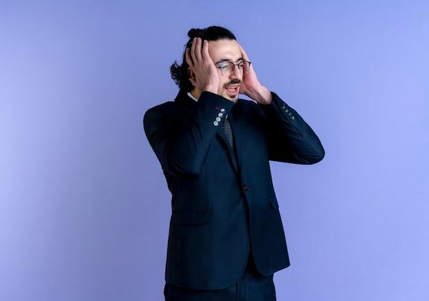 Uomo d'affari in abito nero e occhiali che osserva da parte tenendo la testa con le mani confuse e molto ansiose in piedi oltre il muro blu Foto Gratuite