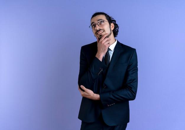 Uomo d'affari in abito nero e occhiali guardando da parte con la mano sul mento sorridendo e pensando in piedi sopra la parete blu Foto Gratuite