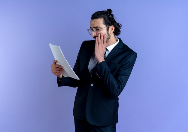 Business man in black suit and glasses looking at documents worried with hand on his face standing over blue wall Free Photo