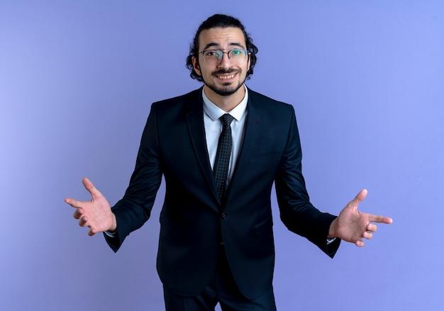 Uomo di affari in vestito nero e occhiali che guardano al fronte sorridente che fa gesto di benvenuto con le mani in piedi sopra la parete blu Foto Gratuite