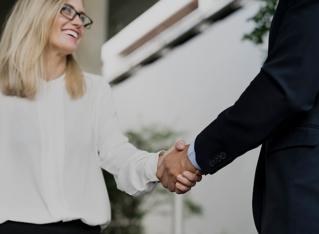 Business man and business women shaking hands in agreement Premium Photo