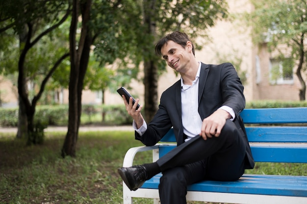 Business man checking his phone in park Free Photo