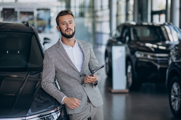 車のショールームで車を選ぶビジネスマン 無料写真