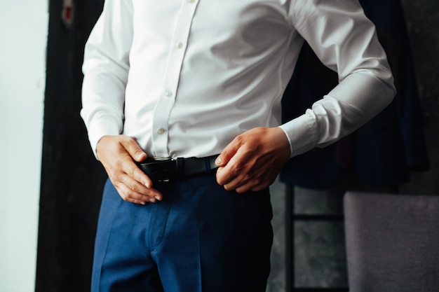Business man in dark trousers and a white shirt fastened a black leather  belt close up. men's formal outfit. handsome guy  puts on suit Premium Photo