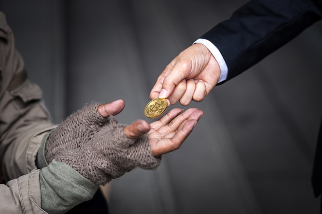 Business man give his gold bitcoin to homeless man Premium Photo