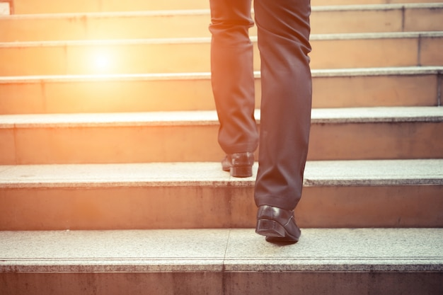 Business man going up the stairs  in a rush hour to work. hurry time. Premium Photo