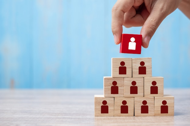 Business man hand placing or pulling red wooden block with person Premium Photo