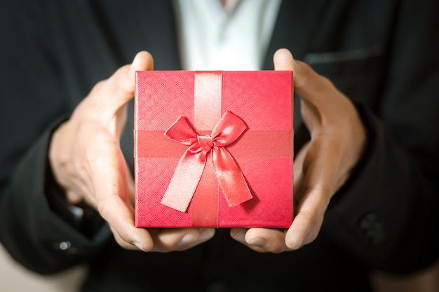 Business man hold red gift box in hands. Premium Photo