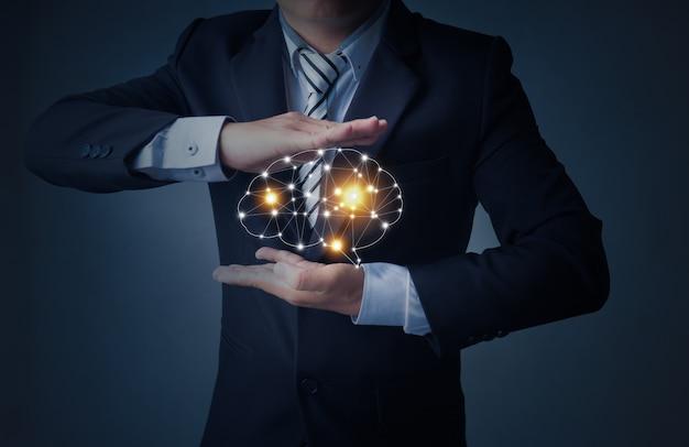 Business man holding a brain in palm Premium Photo