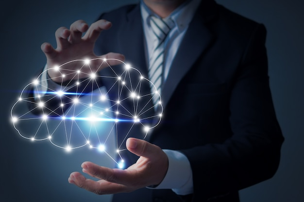 Business man holding a brain in palm Premium Photo