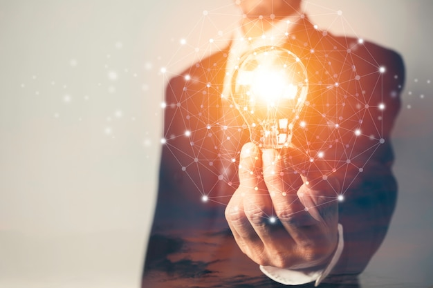 Business man holding a light bulb with coins money and copy space for accounting, ideas and creative concept. Premium Photo